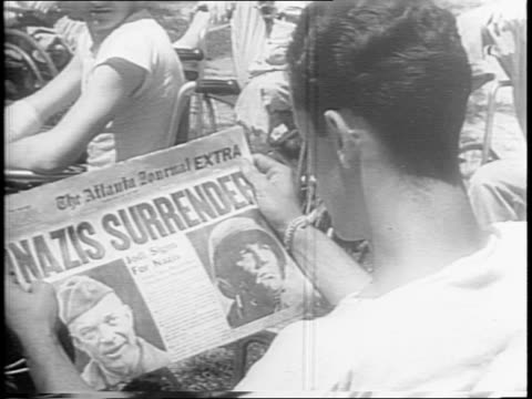 vídeos de stock, filmes e b-roll de newspaper reads 'germany surrenders' / crowd rejoices in the streets of times square / man in crowd impersonates hitler / fred vinson speaks on the... - 1945