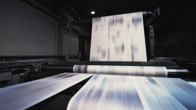 cs newspaper sheet being cut into pages by the machine in the printing factory - pressa da stampa video stock e b–roll