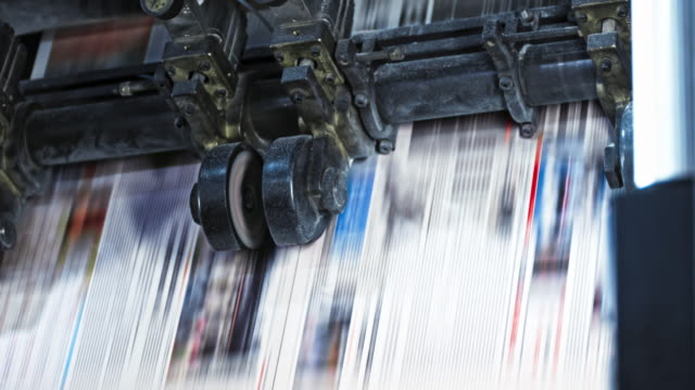 vídeos de stock e filmes b-roll de ld newspaper sheet being cut while coming out of the printing press - jornal