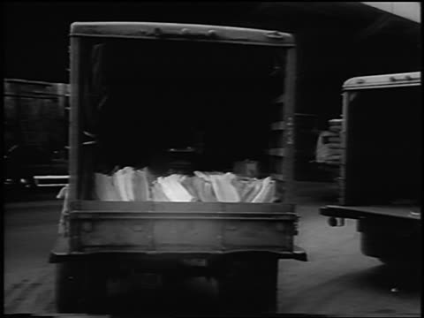 B/W 1963 REAR VIEW newspaper truck driving away / PAN to partial view of NYC skyline