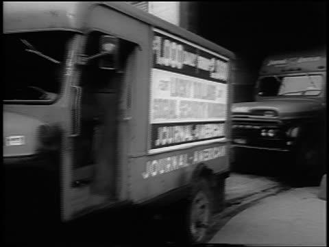 B/W 1963 newspaper trucks pulling out of building / NYC / newsreel