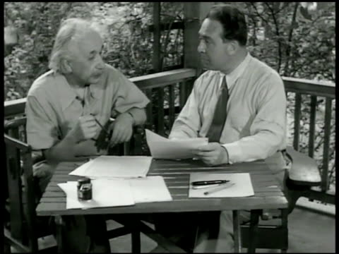 newspaper w/ albert einstein on cover 'einstein evolves new theory' 1939: theoretical physicist albert einstein w/ physicist dr. leo szilard at table... - アルバート・アインシュタイン点の映像素材/bロール