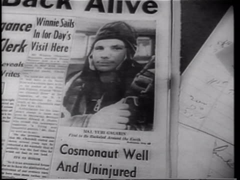 "newspaper with ""reds orbit man"" headline and photo of yuri gagarin as the first man in space / yuri gagarin in uniform walking outdoors / crowd of... - newspaper headline stock videos & royalty-free footage"