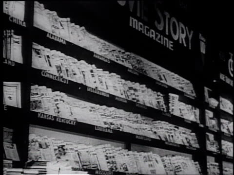 1945 montage newspapers and books on a printing press, in a library and in newsstands / united states - pressa da stampa video stock e b–roll