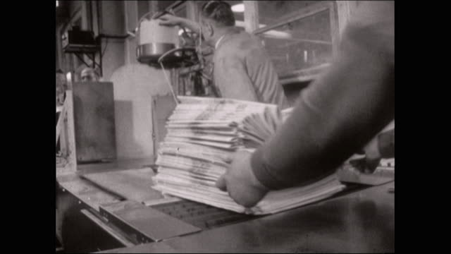 newspapers being bundled on packing line - bbc archive stock-videos und b-roll-filmmaterial