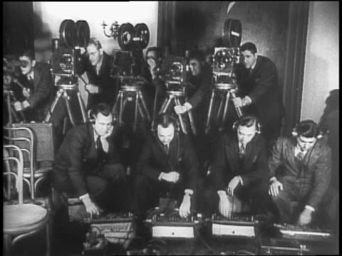 newspapers coming off press / closeup of hands turning radio dials labeled with different countries / row of cameramen and sound equipment operators... - mezzo d'informazione video stock e b–roll