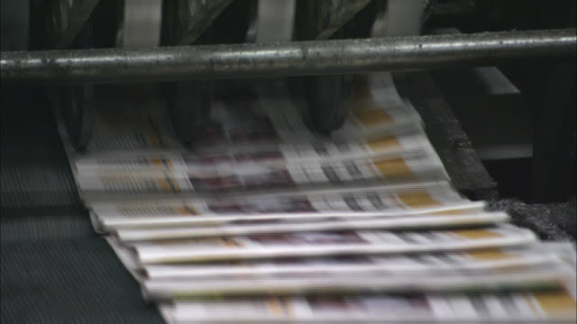 ms newspapers emerging from printing press on conveyor belt/ brazil - druckmaschine stock-videos und b-roll-filmmaterial