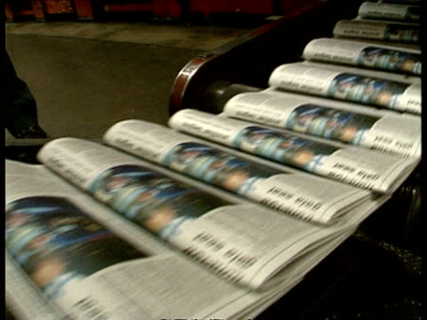 ms newspapers moving along conveyor belts in printing factory, hand removes several copies - mass media video stock e b–roll