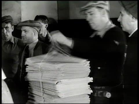 stockvideo's en b-roll-footage met newspapers rapidly coming out of folding machine male standing near others bundling newspapers into large pile cu male hands sitting pile of new york... - 1949