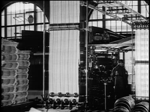 b/w 1919 newspapers running on printing presses in plant as 2 men work nearby / newsreel - press room stock videos & royalty-free footage