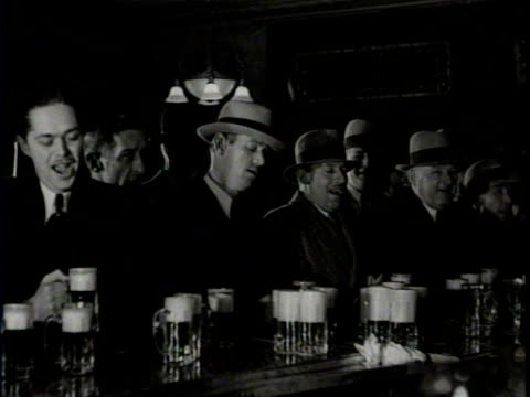 vidéos et rushes de newsreel / a bar is crowded with beer drinkers as prohibition ends / the bartender fills the glasses with beer / he slides glasses of beer down the... - prohibition
