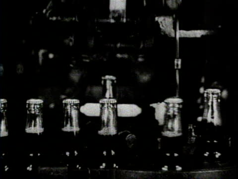 newsreel / a milwaukee brewery prepares for a change in the volstead act / beer bottles move forward on an automated conveyer belt / machines fasten... - beer cap stock videos & royalty-free footage