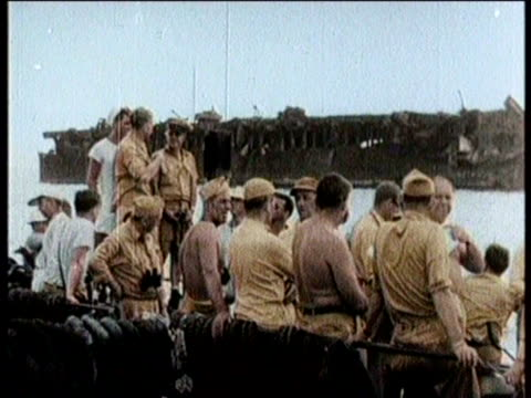 newsreel / atomic bomb detonated at bikini atoll in the marshall islands / sailors float on boat / sailors use water hose / charred exterior of ship... - nuclear fallout stock videos & royalty-free footage