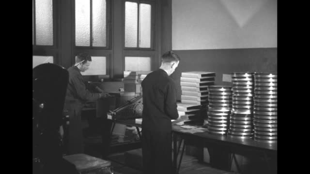 vs newsreel being threaded onto movie reels packaged and labeled according to city / film being inspected / vs men and working with film and film... - film reel stock videos & royalty-free footage