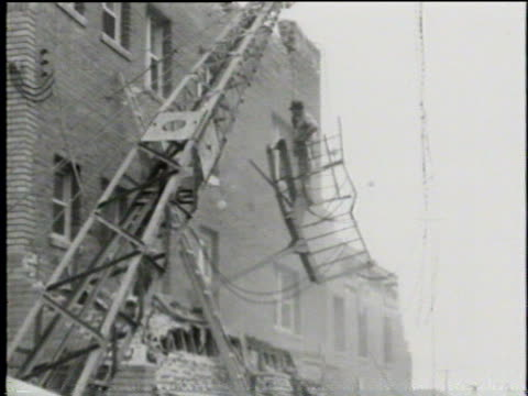 stockvideo's en b-roll-footage met newsreel / cleanup crews complete the demolition of partially collapsed buildings after a devastating earthquake / woman walks through room with no... - 1933