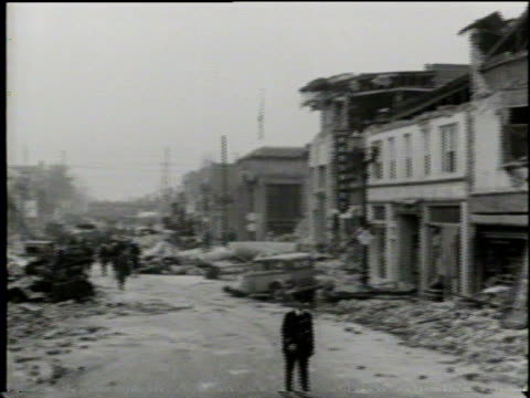 stockvideo's en b-roll-footage met newsreel / cleanup crews sweep up rubble in a city street devastated by earthquake / a bulldozer pushes rubble into a massive pile of debris / - 1933