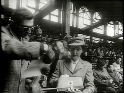 newsreel / cold war / red cross workers pass out documents on recommended fan conduct at ebbets field in brooklyn new york / two red cross workers... - ebbets field video stock e b–roll