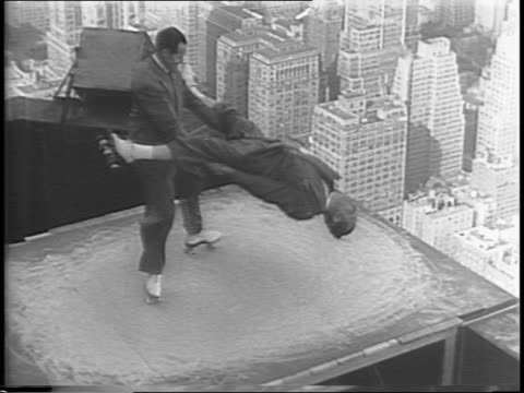newsreel / earl and jack of the skating earls skate atop the empire state building on a platform 87 stories up / that's higher than the price of beef... - ace stock videos and b-roll footage
