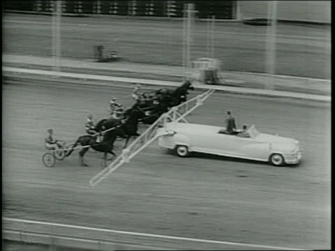 Newsreel / Harness Racing / A new starting gate to start harness racing a white automobile on the track / Steve Phillips the inventor adjusts the...