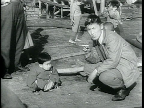 newsreel / japanese citizens prepare to return to their homeland/ children lay on luggage/ people line up to board a ship/ a soldier helps a little... - 1940~1949年点の映像素材/bロール
