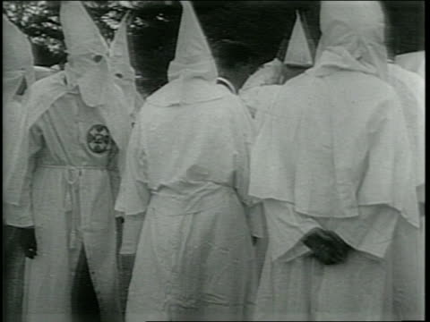 vídeos de stock, filmes e b-roll de newsreel / ku klux klan back in south / a group of men in white robes not all with hoods on / men in white robes milling about / - ku klux klan