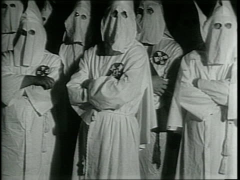 vídeos de stock, filmes e b-roll de newsreel / ku klux klan back in south / footage from a kkk film made in 1937 men in robes and hoods / some hoods have different states on the side of... - ku klux klan