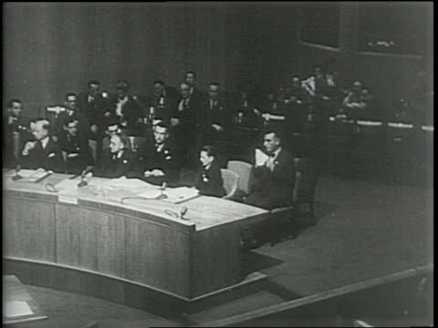 Newsreel / Narrated / A huge group of politicians sit at a curved table / The politicians raise their hands to cast a vote / Suddenly Soviet...
