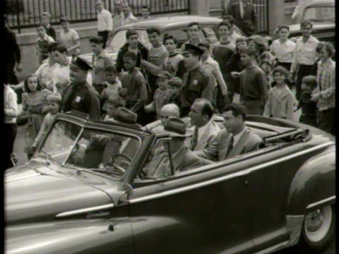 newsreel / narrated / baseball hero is driven through town as kids walk along the car / he stops to wave at the fans / police officer keeps kids away... - narrating stock videos and b-roll footage