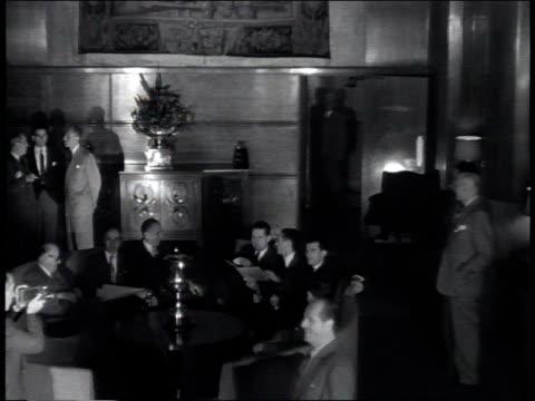 vidéos et rushes de newsreel / narrated / businessmen enter the international house for meeting / businessmen enter large room with round table /businessmen walk past... - raconter