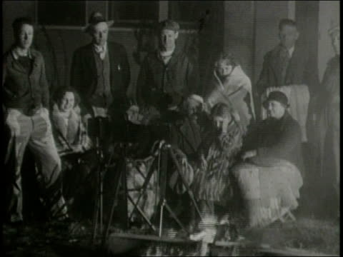 vídeos de stock, filmes e b-roll de newsreel / narrated / crowds stand around campfires and buildings destroyed by an earthquake / a woman explains what it was like for her when the... - narrating