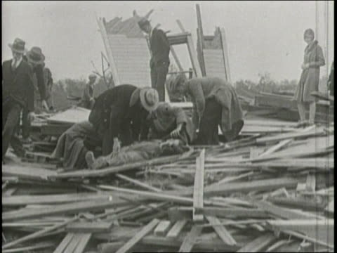stockvideo's en b-roll-footage met newsreel / narrated / groups of civilians and police officers sift through the rubble of collapsed buildings rescuing injured people after earthquake... - 1933
