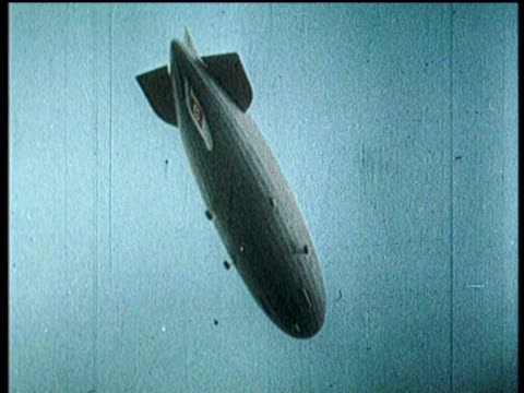 newsreel / narrated / hindenburg travels smoothly to new jersey before crashing on may 06 1937 in lakehurst new jersey / the hindenburg gliding over... - ヒンデンブルク号点の映像素材/bロール