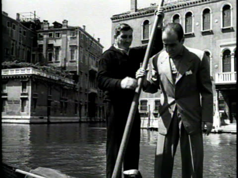 newsreel / narrated / humphrey bogart and lauren bacall sit in a gondola in a venice canal / a narrator speaks in italian / humphrey bogart has a go... - humphrey bogart stock videos & royalty-free footage