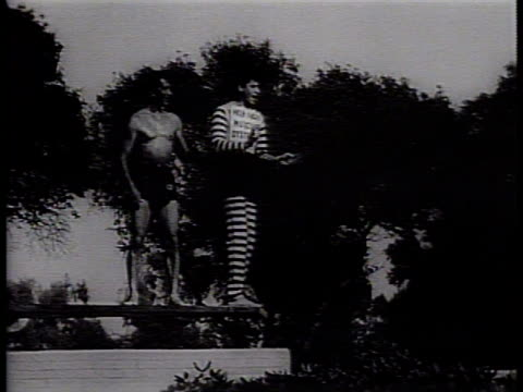newsreel / narrated / jerry lewis pretends to be afraid to jump off a diving board / dean martin pushes jerry lewis off the diving board / an... - narrating stock-videos und b-roll-filmmaterial