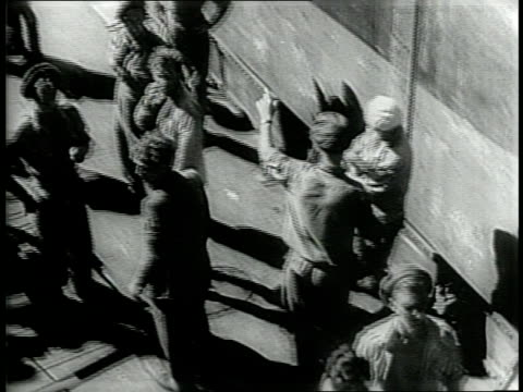 newsreel / narrated / on a ship in palestine a few men try to hold another man down on the floor / the ship is crowded with onlookers / more people... - 1946 stock-videos und b-roll-filmmaterial