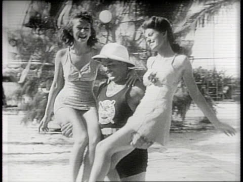 newsreel / narrated / paramount news / santa claus at the beach in miami florida in 1940 / women swim out of the pool and sit on the edge / santa... - at the edge of stock videos & royalty-free footage