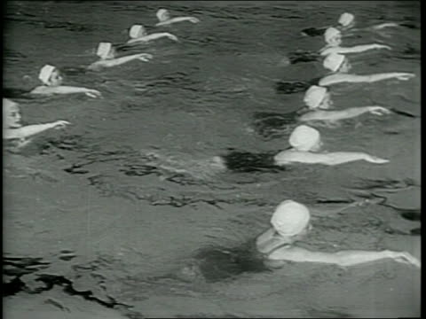 vidéos et rushes de newsreel / narrated / smith college lifeguards perform a display of synchronized swimming at an mit swimming pool / women dive into pool / various... - raconter