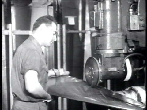 newsreel / narrated / the propeller tube is moved to a conveyor belt / a sheet grinder gives a piece of steel / a worker welds the steel / - narrating stock videos & royalty-free footage