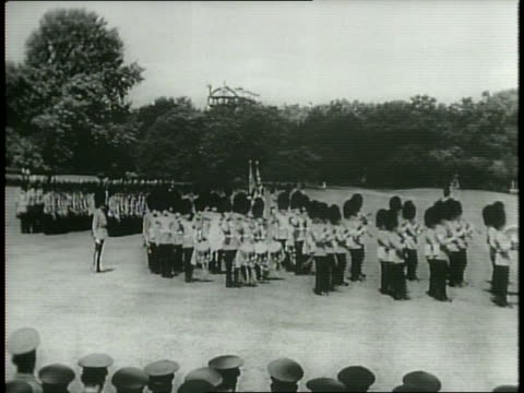 vídeos de stock e filmes b-roll de newsreel / narrated / welsh guards in uniform march outside buckingham palace / king george vi exits buckingham palace wearing a welsh guard uniform... - 1949