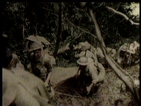 newsreel / narrated / world war 2 / planes fly over new guinea / the jungle is steaming / australian troops march / troops pass a native / troops... - seconda guerra mondiale video stock e b–roll