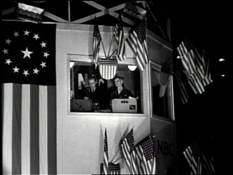vídeos de stock, filmes e b-roll de newsreel / nbc broadcasts from a booth / the booth is surrounded by flags / the radio announcers call in tests / - comentarista