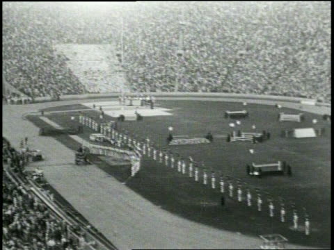 newsreel / no audio / 1932 summer olympics closing ceremonies los angeles / wide shot of closing ceremony with line of men in white uniforms with... - olympic torch stock videos & royalty-free footage