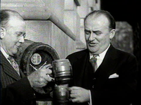 vidéos et rushes de newsreel / no audio / a group of men give a presentation outside of a brewery / a beer barrel sits between two of the men / they pour the first cups... - prohibition