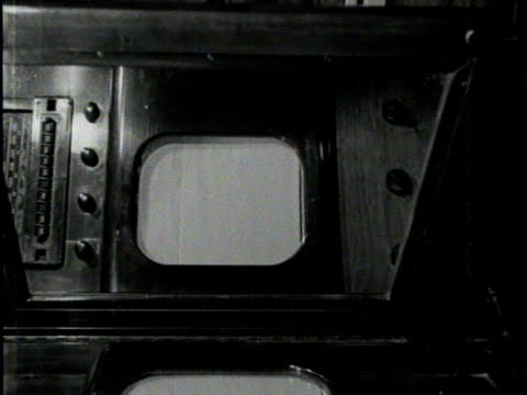 stockvideo's en b-roll-footage met newsreel / no audio / a man sits in front of an early television set / close up of television / - 1930