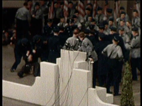 newsreel / no audio / a nazi supporter speaks to an audience and his podium shakes as a man attempts to run away from the stage / nazi supporters... - anno 1938 video stock e b–roll