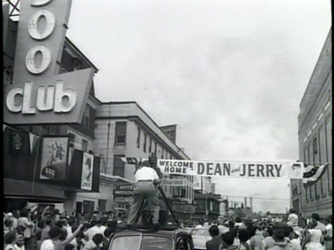 newsreel / no audio / a sunny beach and boardwalk / jerry lewis and dean martin joke together / an airplane flies a banner that welcomes lewis and... - ホームカミング点の映像素材/bロール