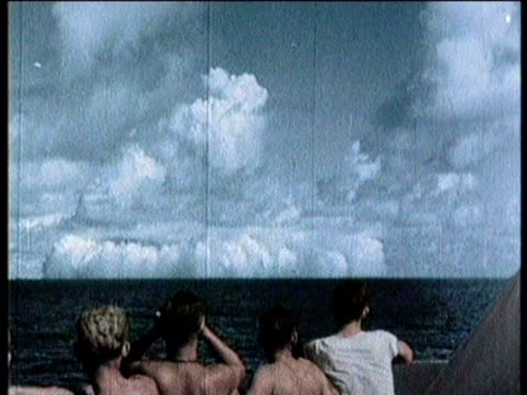 Newsreel / No audio / Atomic bomb tested at Bikini Atoll in Marshall Islands in 1960 / Arial view of ship in ocean / Sailors watching mushroom cloud...