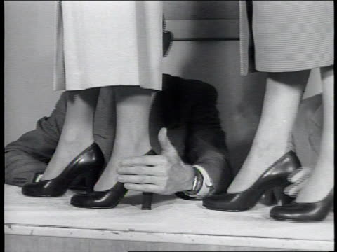 newsreel / no audio / business men sit at a long table as women in dress shoes walk across the table / the women line up in a row and turn to the... - dress shoe stock videos and b-roll footage