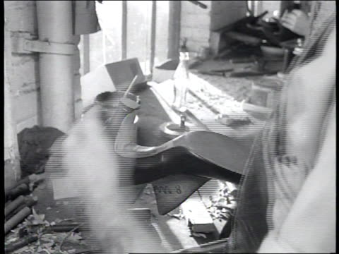 newsreel / no audio / factory workers make shoes at the brown shoe company / a worker attaches a heel to a dress shoe with the help of a machine / - dress shoe stock videos & royalty-free footage