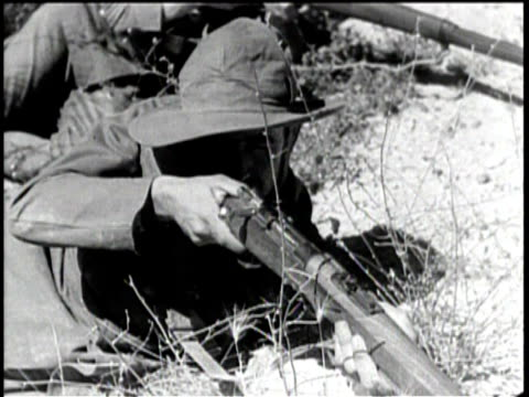 newsreel / no audio / men handling rifles / two soldiers showing woman how to arm a rifle / men with guns in truck drive by men on ground with guns /... - 1938 stock-videos und b-roll-filmmaterial